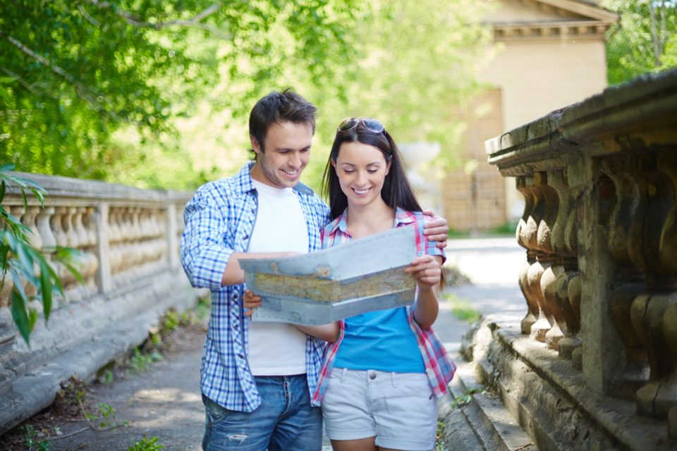 Portrait of travelers with map visiting ancient town