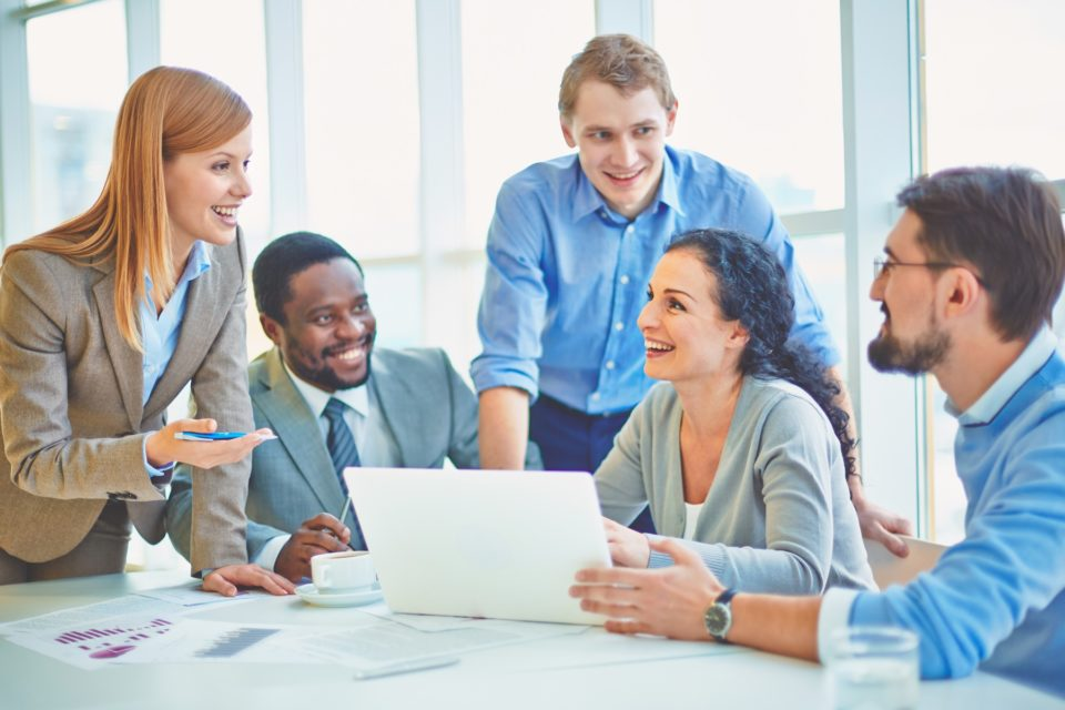 Group of business partners looking at smiling female explaining her ideas at meeting